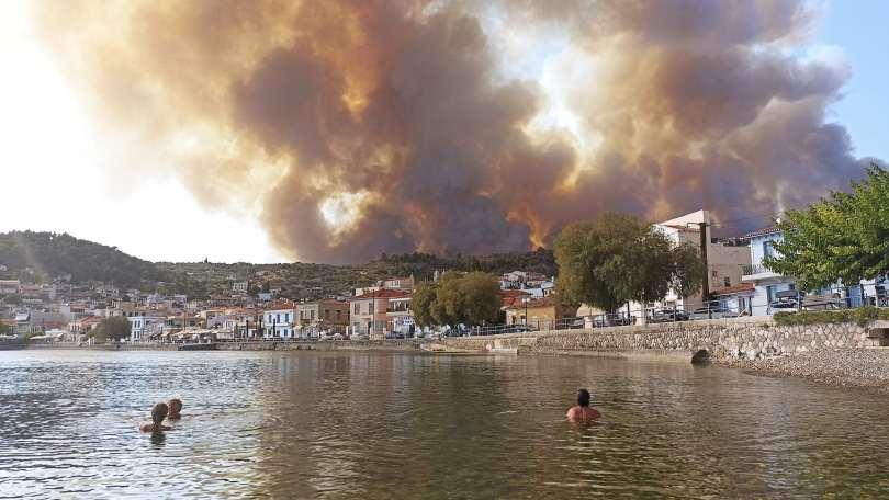 People swim in lake with bushfire smoke in the horizon