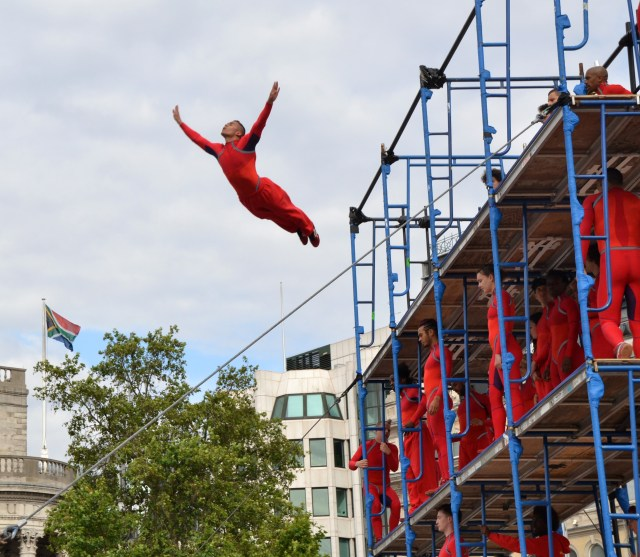 A dancer in a red unitard flies off a scaffolding structure in Central London