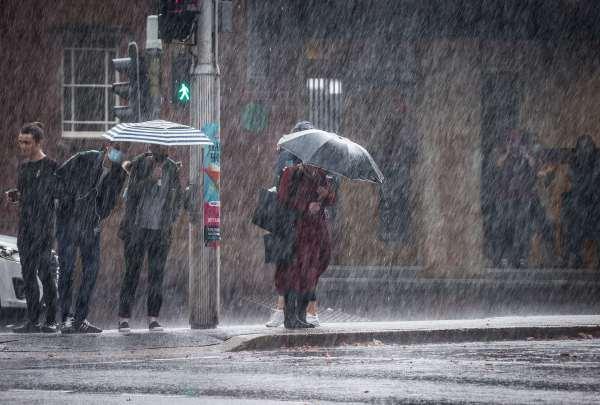 people queue in heavy rain