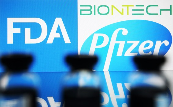 Vaccine vials lined up in front of the FDA and Pfizer BioNTech logos