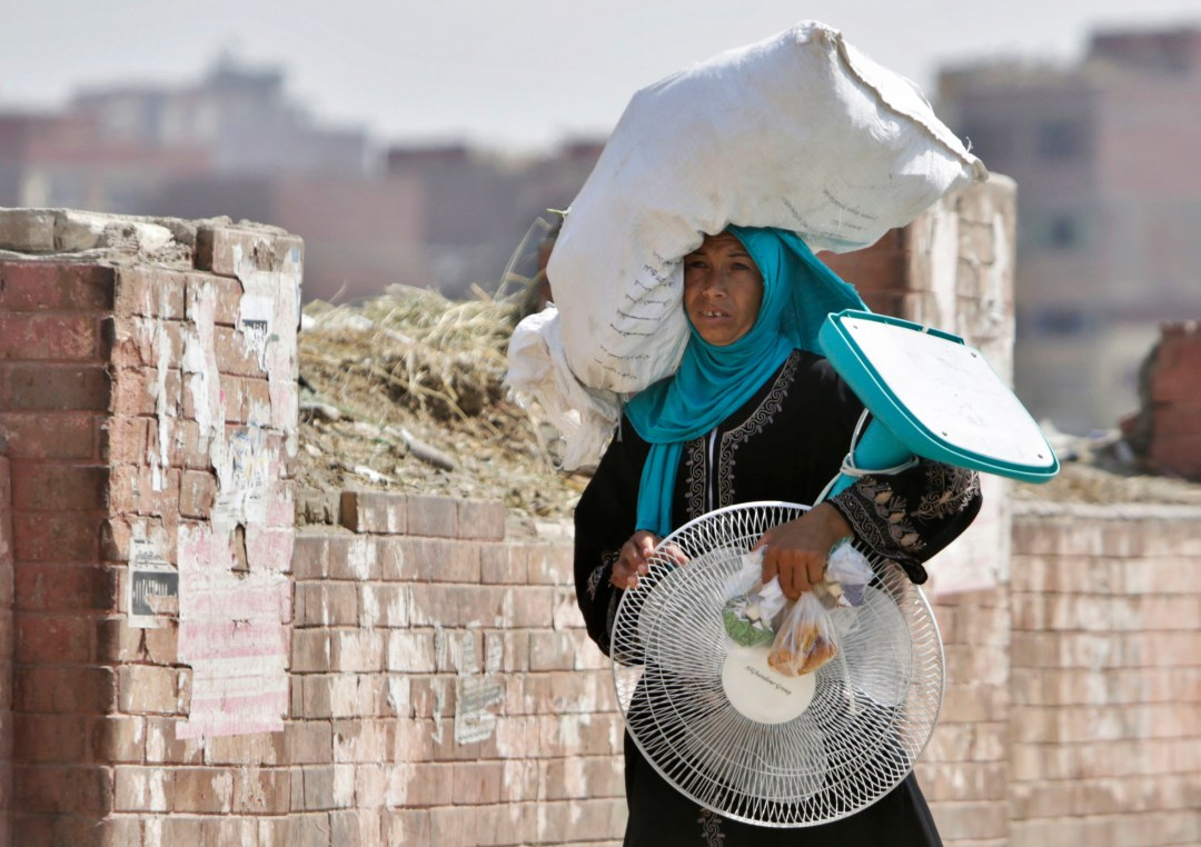 woman carries fan and sack