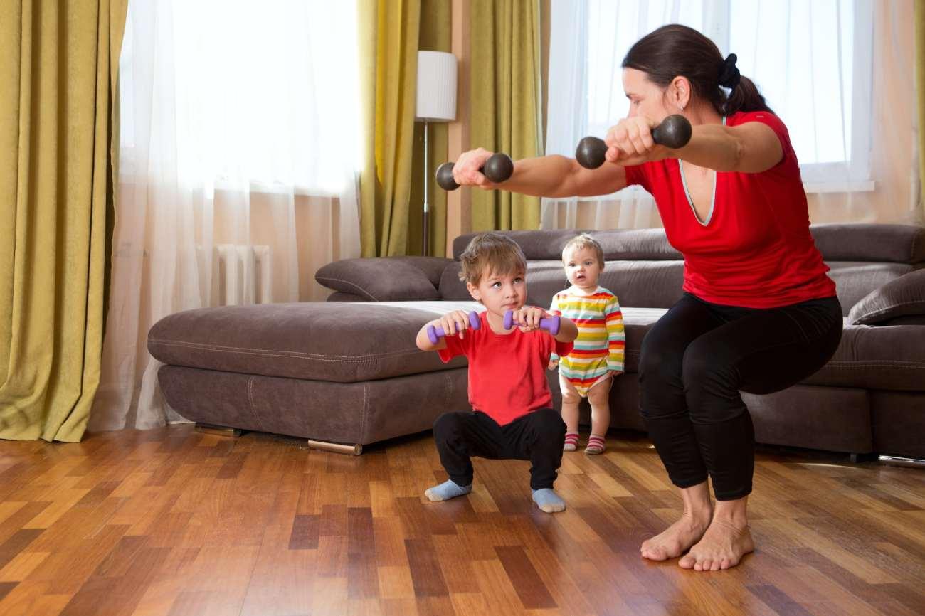 Una donna si allena a casa con i bambini.