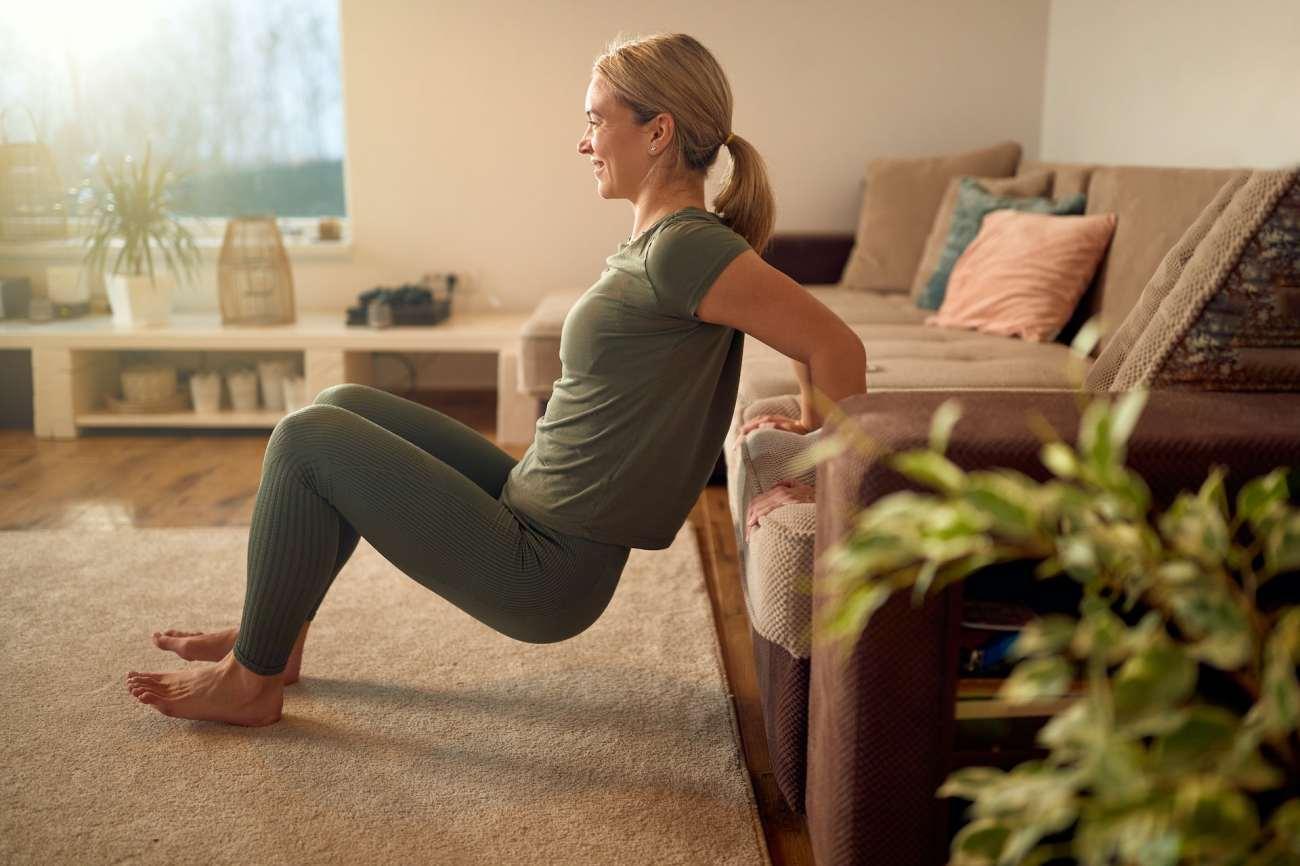 Una donna fa i tuffi per tricipiti a casa.