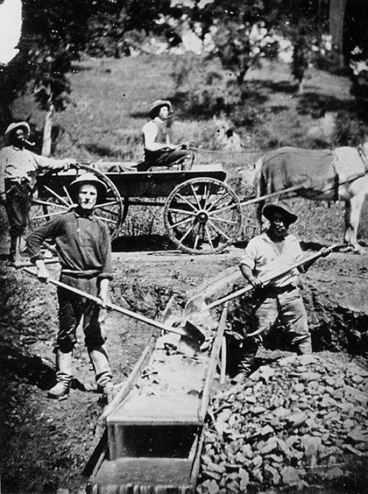 iew of 4 men, two miners at work on a long tom (one man is an African American), one man in a wagon, one man standing behind the wagon.