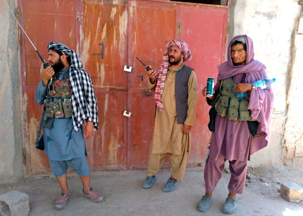 Three Taliban fighters stand guard at a checkpoint