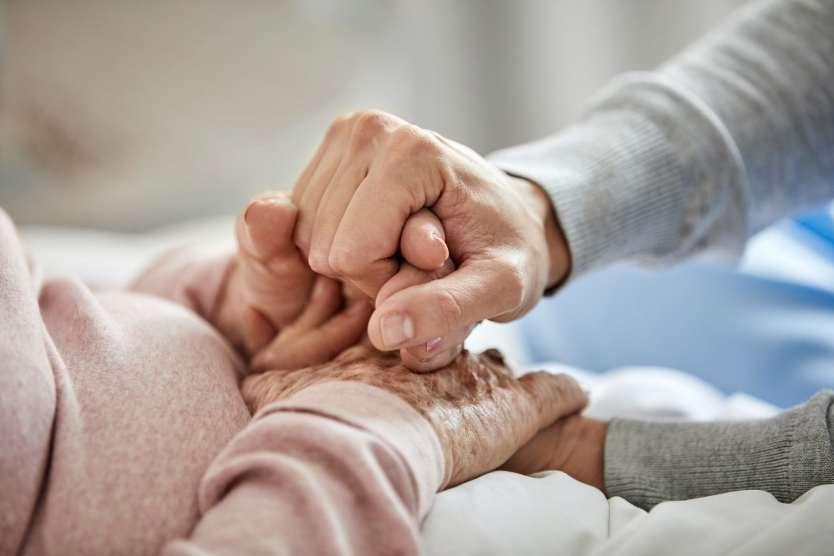 Caregiver holding the hands of an older adult.