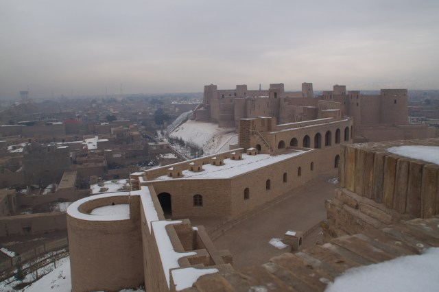 A large fortified building overlooks a city