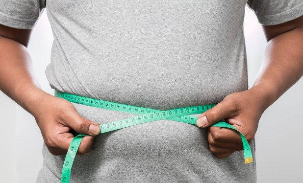 Overweight man using a measuring tape to measure his midsection.