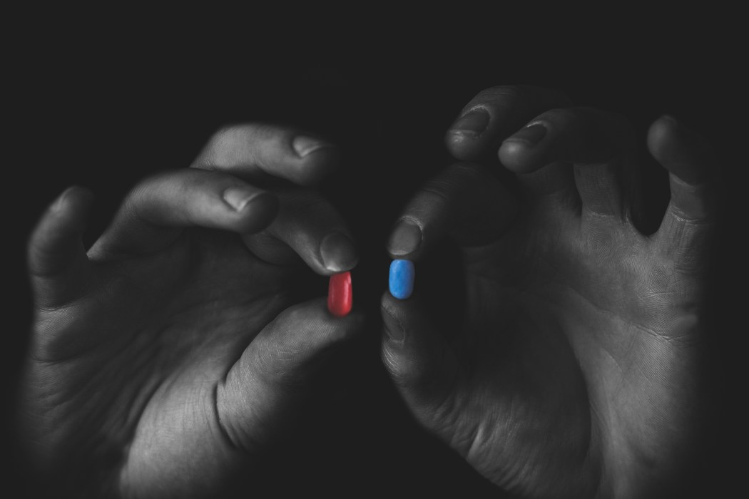 Two hands holding up a red and a blue bill. Other than the pills, the image is in black and white.