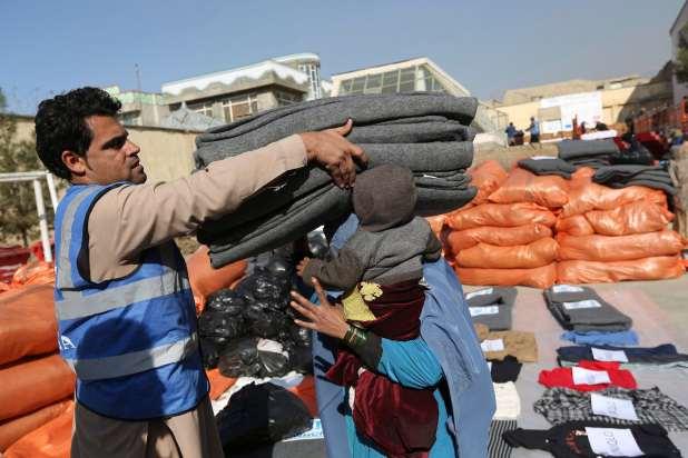 A UNHCR employee hands an Afghan woman sacks of supplies