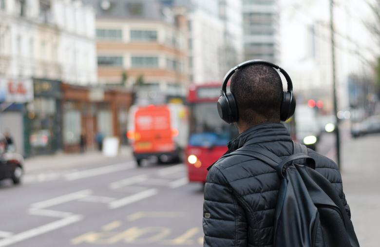person with headphones waiting for a bus