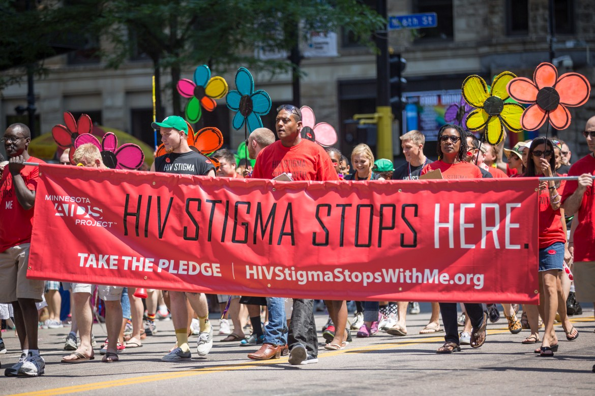 People in a parade carrying a banner that reads 'HIV Stigma Stops Here.'