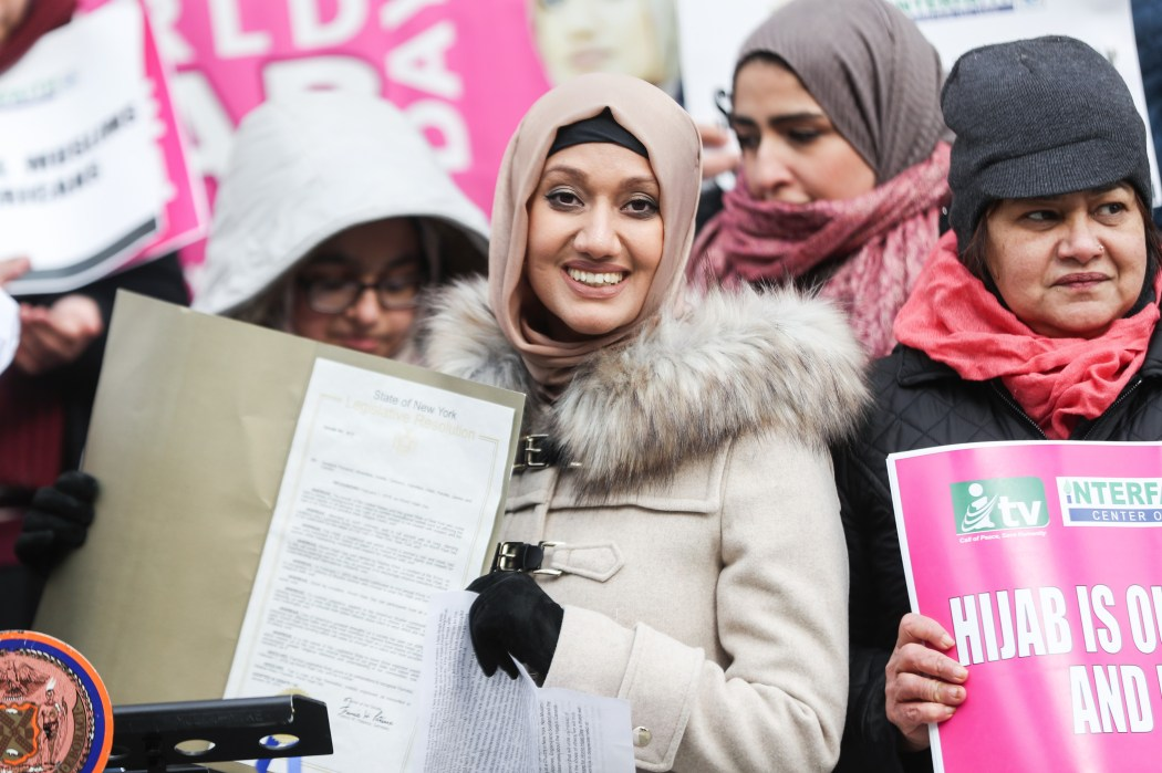 women gather on world hijab day while holding pink posters