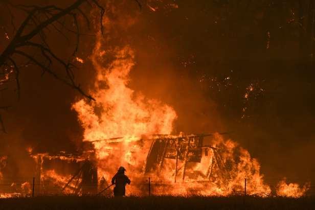 firefighter and bushfire engulfing house