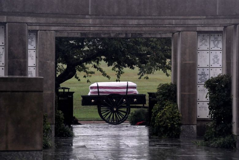 The casket of a US soldier is seen through a doorway during a full military honors burial ceremony