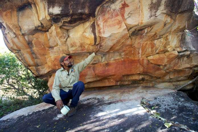 A man sitting near rock art in North Kimberley.