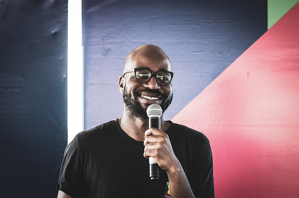 against a backdrop of angular colour block paintings, a bald bearded man in glasses smiles as he talks into a microphone.