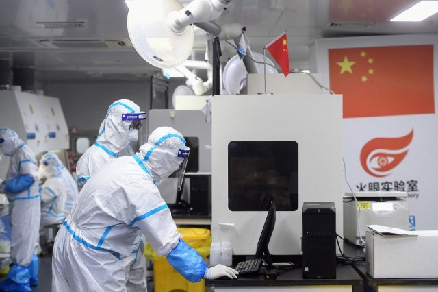 Des techniciens en tenues protectrices travaillent sur des échantillons dans un laboratoire de Wuhan