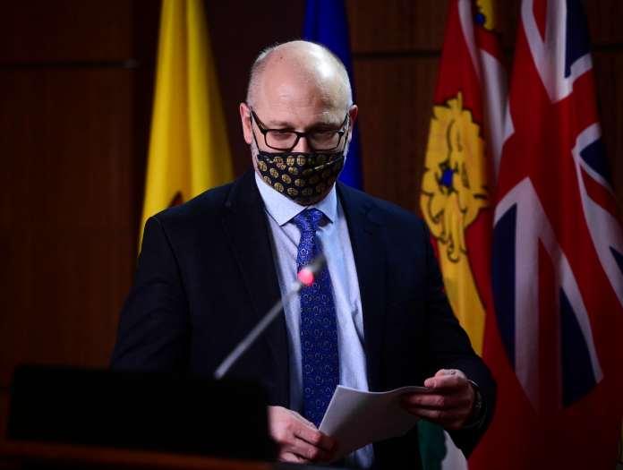 David Lametti wearing a face mask standing on the podium