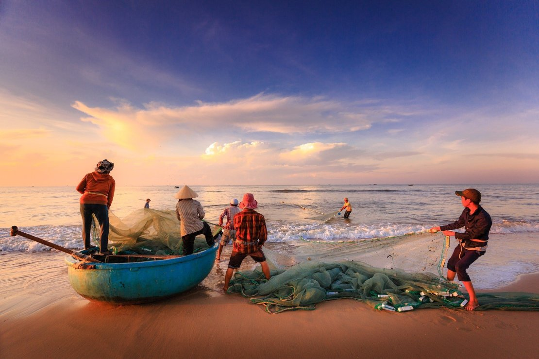 Fisherman haul in a catch on a beach