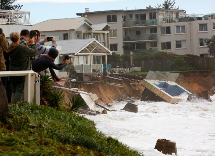Tourists photograph beachside homes damaged by storm