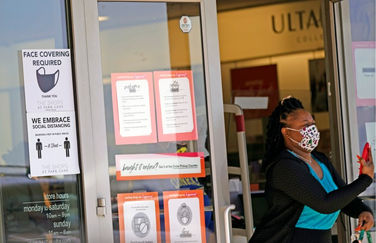 A woman exiting a store with signs showing mask requirements on the door.