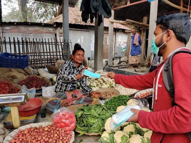 A man wearing a surgical mask handing a mask to a woman working at a vegetable stand.