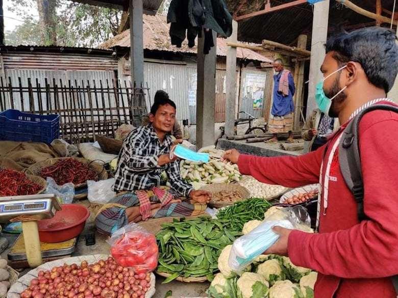 Un hombre que lleva una mascarilla quirúrgica entrega una mascarilla a una mujer que trabaja en un puesto de verduras.