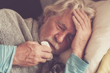 Older man with cold symptoms lays down, wrapped in a blanket, cradling his head, holding a tissue to his nose.