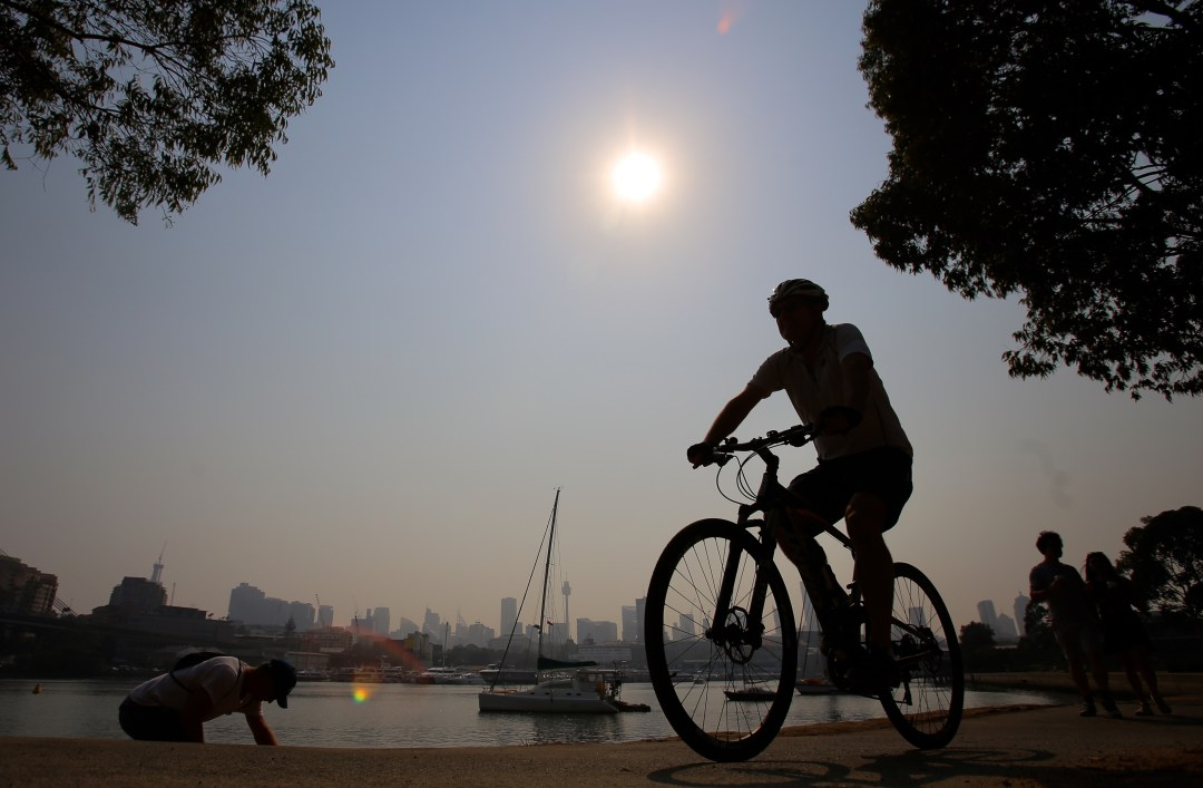 Silhouette of cyclists against sun and water