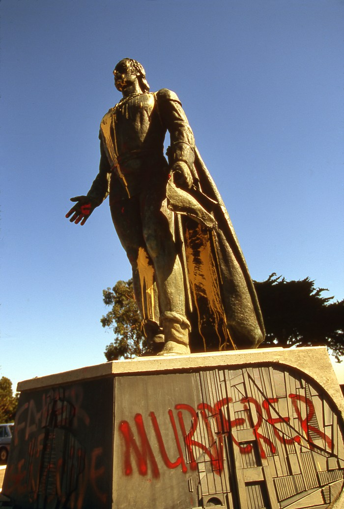 A statue of Christopher Columbus is vandalized with the word 'murderer' sprayed in red.