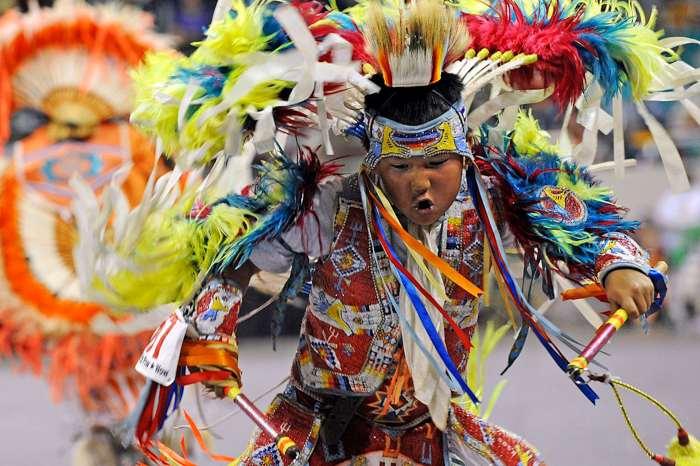Boy dressed in colorful ceremonial garb dances.