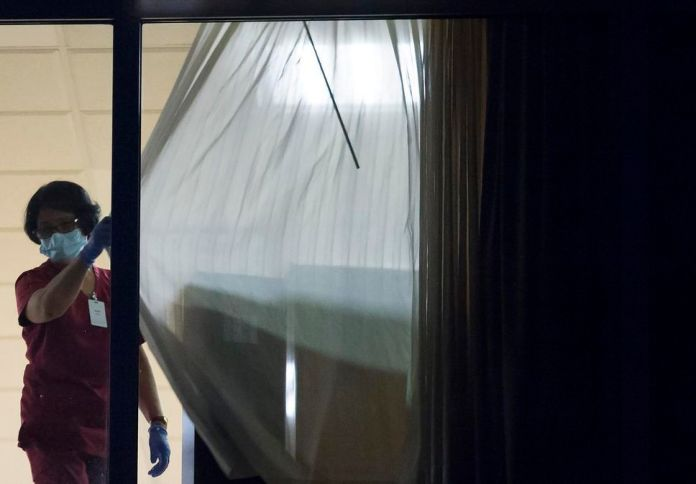 A worker is seen closing the curtains at the Lynn Valley Care Center in Vancouver in this file photo from March 25, 2020. After outbreaks in nursing homes across the country, seniors' advocates and politicians examine the area Canadian long-term care to an unprecedented degree.
