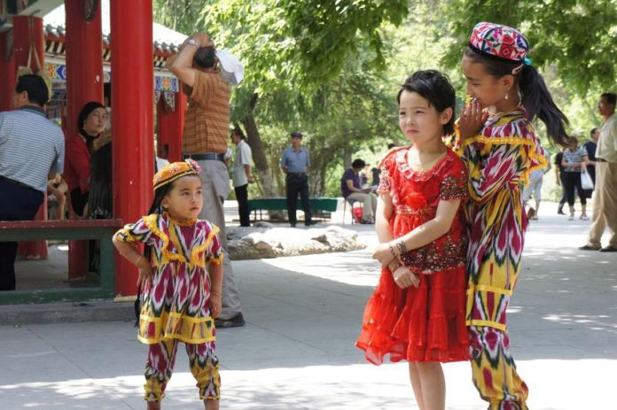 Uygar children play in a park in Tanzan, Xinjiang, before major security restrictions.  Two Canadians, Andrea and Gary Dyke, say they left the area after living there for a decade due to the massive security measures that make life difficult for the ethnic Uygar population in the region and cause fear.
