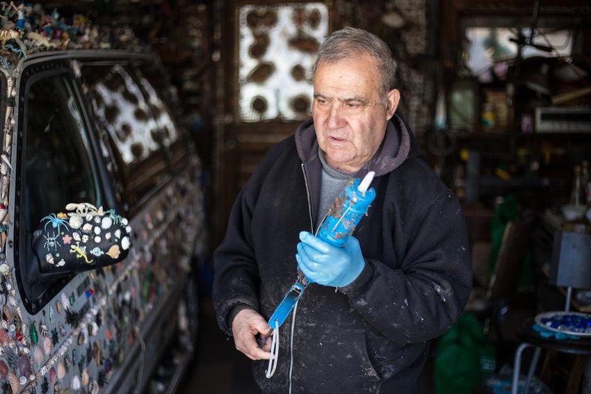 carreira with glue gun - He drives a van covered in plastic bugs. And he's made Toronto's most eccentric garden his life's work