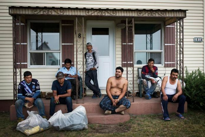 A group of Mexican migrant workers after finishing their work on a nearby farm, Ky.  K sits on the front porch of a house in Lavaltree.  A STAR investigation in 2019 revealed thousands of complaints made by migrant workers to Mexican authorities over a decade, and housing issues were the most common problem.