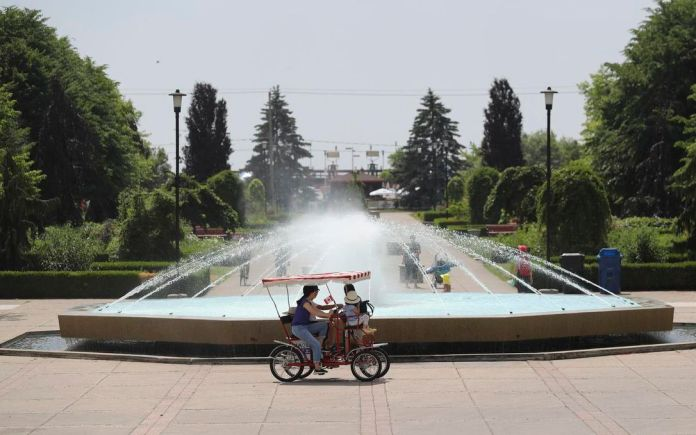 On Friday, a two-seater bike circles the fountain of Center Island, while the islands reopen to the public in the middle of a torrid period of time.