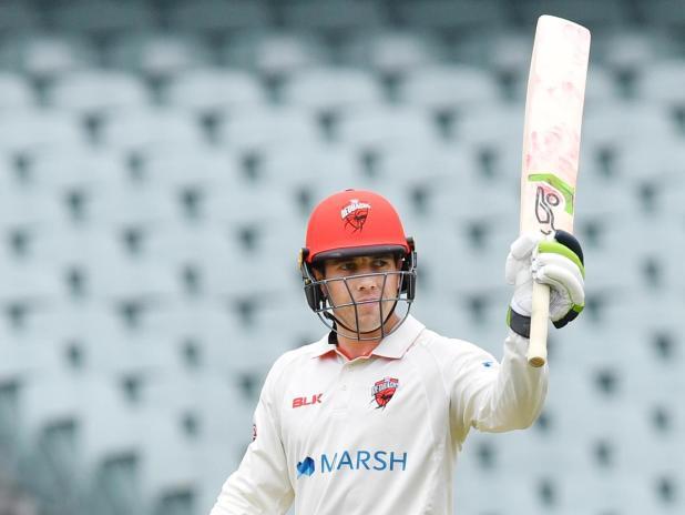 Harry Nielsen raises his bat after scoring 50 runs during the Marsh Sheffield Shield match between the South Australia Redbacks and Western Australia.