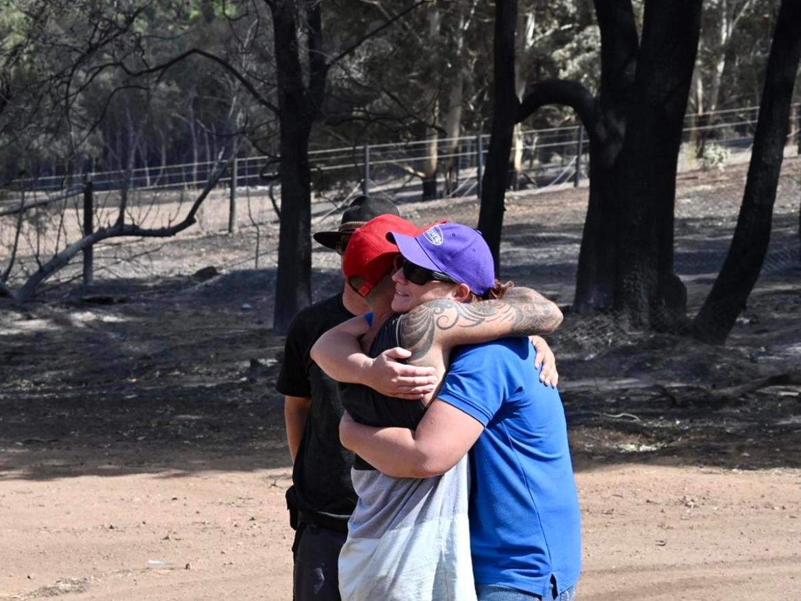 Lee Lyons is consoledafter visiting hishome, which wasgutted by the bushfire.