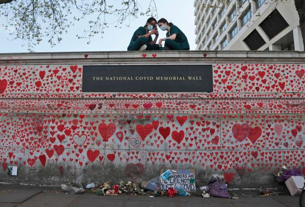 Nurses from the nearby St Thomas' hospital sit atop the National COVID Memorial Wall in London.