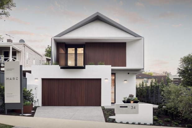 The custom build's elevation features a projecting angular gable surrounding the top-floor front balcony, white feature brickwork and Biowood cladding.