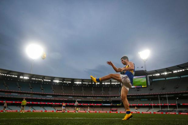 Andrew Gaff kicks the ball in an empty MCG.