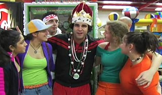 Man wearing a crown is surrounded by women in a video arcade