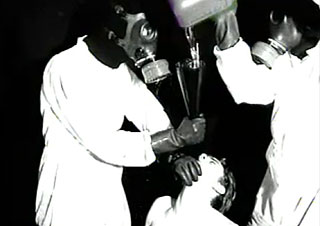 Two mean wearing gas masks pour gasoline down a naked man's throat
