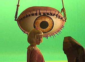 Young blond girl standing in front of a giant eyeball