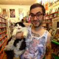 Man in video store holding cat
