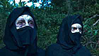 Two people covering their scarred faces with cloth