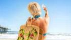 Pretty woman in a bikini taking a selfie on a beach