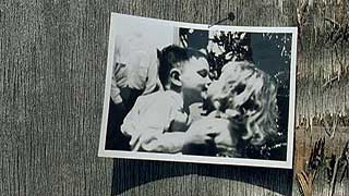 Old B&W photo of a boy kissing a young girl that is nailed to a piece of wood