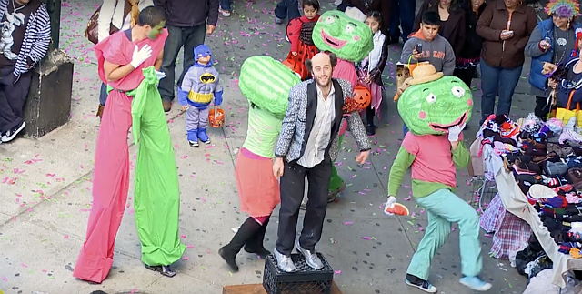 Men with giant green masks dancing in New York City